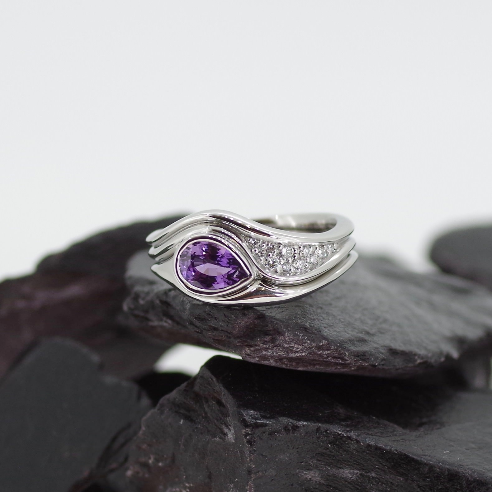 Platinum Corie ring set. Set with one 0.95ct purple pear cut Sapphire with pave set flanking Diamonds (ref ER002)